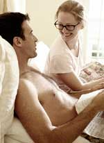 blonde woman with black glasses sitting in bed with husband