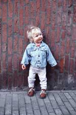 Blonde Toddler in Denim Jacket Standing Against Brick Wall