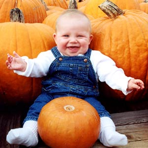 Baby In Jean Overalls With Pumpkin