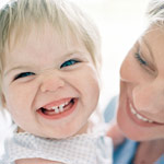 Mom looks at toddler, toothy smile