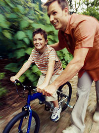 Action shot of brunette father helping brunette son ride bike