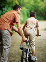 Back shot of brunette father helping brunette son ride bike