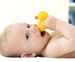 Baby lying on back chewing on rubber ducky