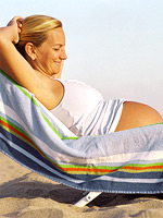 pregnant mom on lounge chair on beach looking at bare belly
