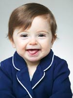 brunette baby girl in blue suit with white piping