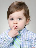 brunette boy with tie and finger in mouth