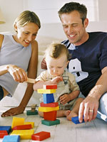 Mom and dad help toddler stock blocks on floor