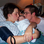 parents kissing newborn
