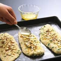 drizzling melted butter evenly over fish with spoon