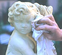 Step 2: Cherub garden statue being wiped with cloth