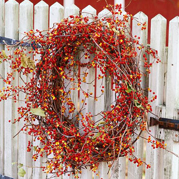 flower and vine wreath on white picket fence