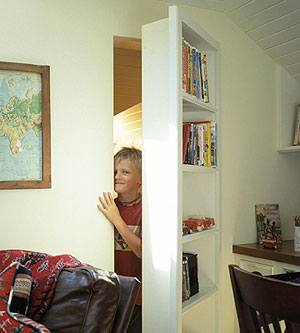 little boy peeking out bookshelf secret passage