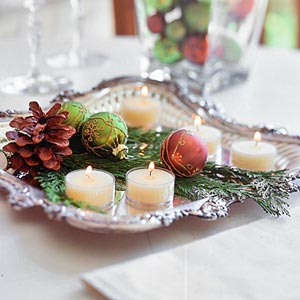 Silver tray centerpiece with candles and pinecones