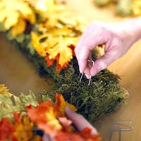 IMWreaths_Person Pinning Leaves Into Rectangular Moss Wreath
