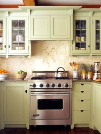 Green kitchen cabinets with tile backsplash behind stove