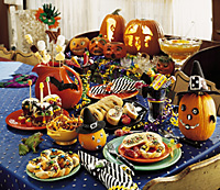 Halloween party table covered with food and treats.