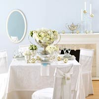 white table setting with flowers and oval mirror on wall