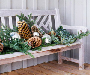 White Weathered Bench Decorated With Pinecones and Pine Garland
