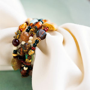 close up of beaded napkin ring on white napkin