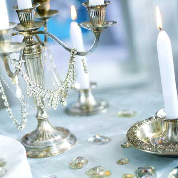 Silver candlesticks with white candles cast the most light around the table