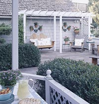Gray deck with arbor and swing.