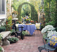 Narrow brick patio with arbor and dining table