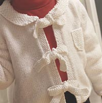 Close up of young girl wearing white tied knit sweater