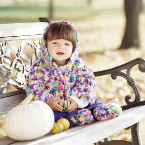 Baby wearing a colorful knit hooded jacket