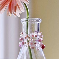 Vintage glass bottle decorated with pink beads as a vase close-up