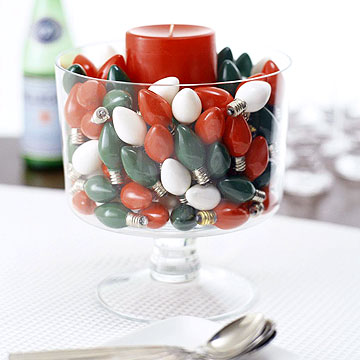 Candle in glass filled with holiday colored light bulbs