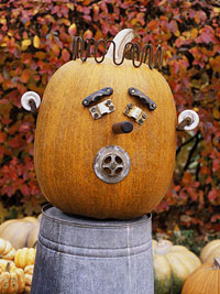 pumpkin decorated with face sitting on tin bucket
