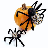 black fake spiders on pumpkin