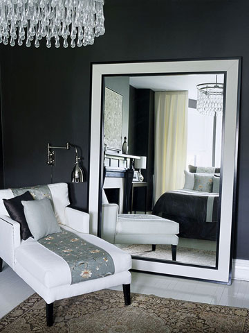 black room with large mirror propped against wall