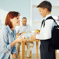 mom handing son packed lunch