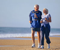 older couple exercise walking on beach