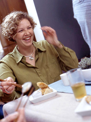 woman in green shirt laughing, holding chopsticks