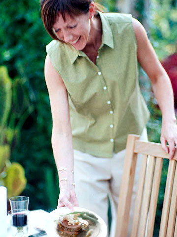 Woman setting plate down at outdoor table
