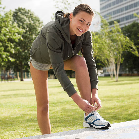 woman in hoodie tying running shoes