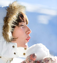 woman in parka blowing on snowball