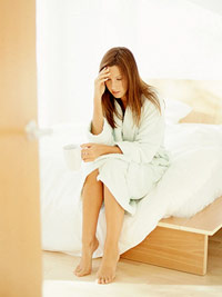 woman in robe sitting on bed massaging head