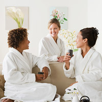 three woman in bath robes drinking tea on sofa
