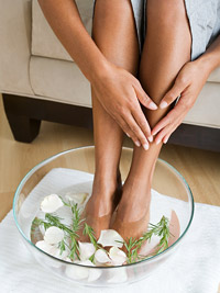 woman soaking feet in herbal water