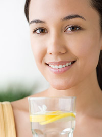 woman holding glass of lemon water