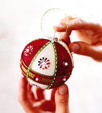 Putting finishing touches on festive felt-covered ornament
