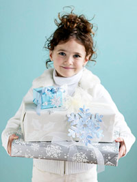 Little girl dressed in white holding silver & white gifts