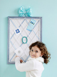 Little girl by blue & white greeting card display board