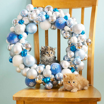 Ornament wreath on brown chair with two kittens