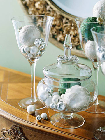 Wine glasses and glass urn filled with white and silver bulb ornaments