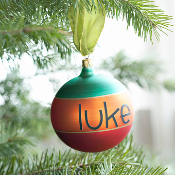 Personalized ornament that says 'Luke' hanging in a tree