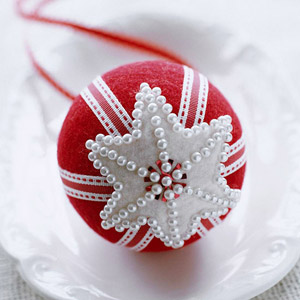 Red felt ornament adorned with pins and ribbons